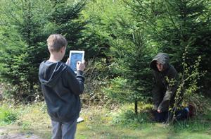 An der frischen Luft macht es nochmal so viel Spaß. Dank der mobilen iPads arbeitet JuMP an vielen Orten. Hier zum Beispiel im Wald. (c) Haus Neuland e.V.
